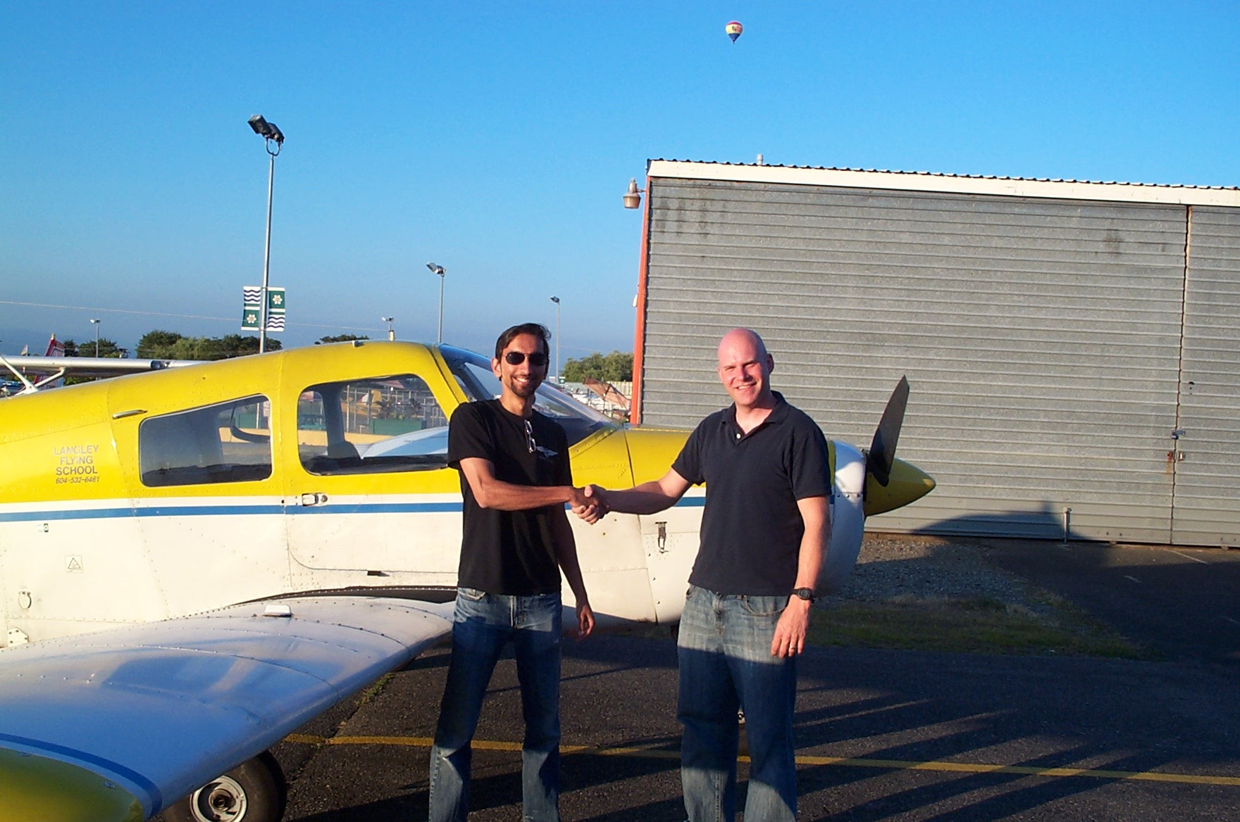 Carl Tingstad receives contrats from his Flight Instructor, Mayank Mittal.  Langley Flying School.