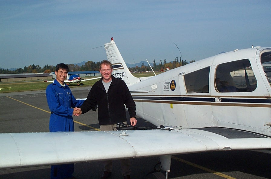 Darren Grant receives congratulations from Flight Instructor Hoowan Nam after the completion of Darren's First Solo Flight on October 26, 2008.