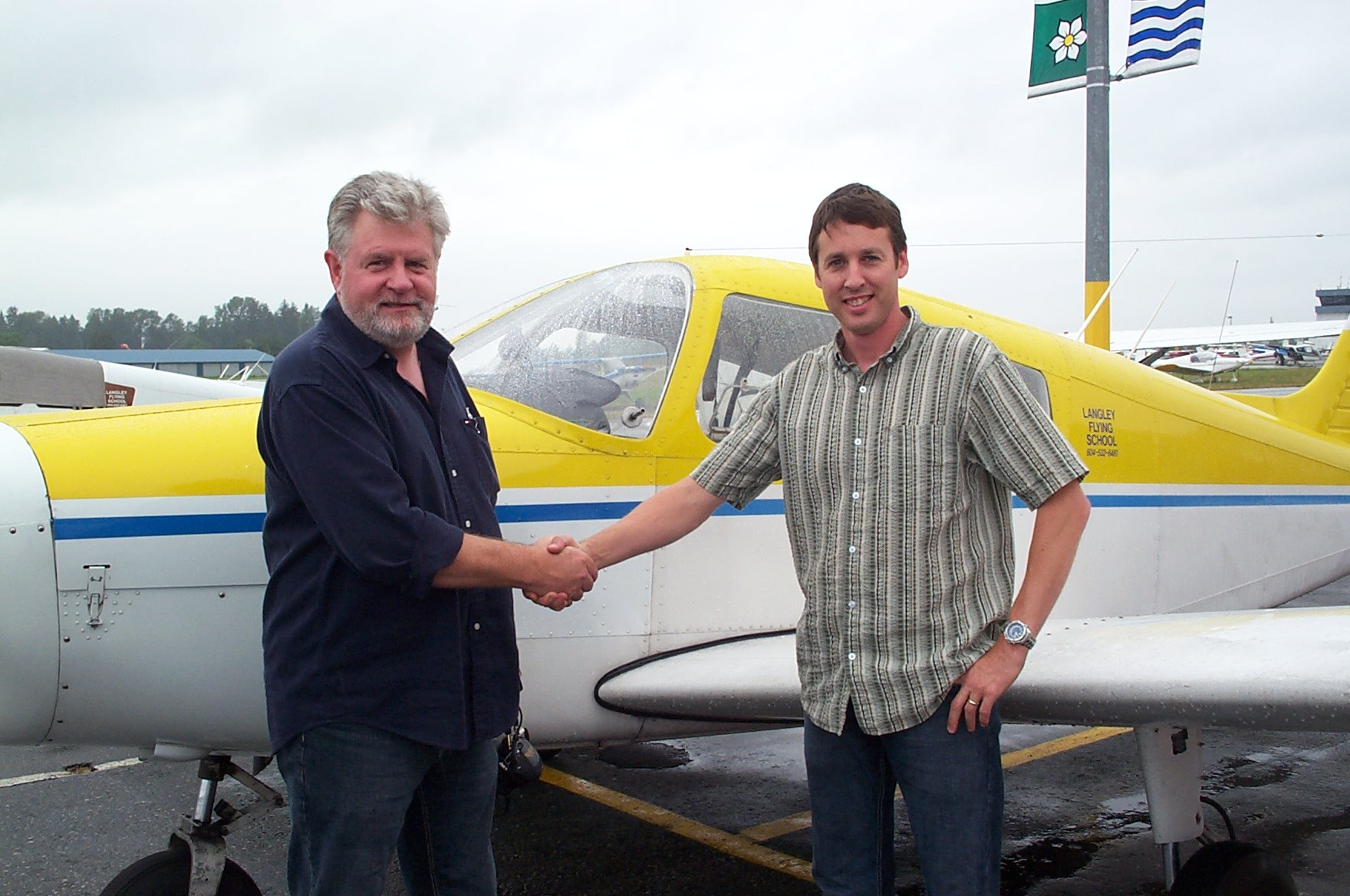 Dean Bicknell receives congratulations from Pilot Examiner Paul Harris after the successful completion of Dean Private Pilot Flight Test.  Langley Flying School.