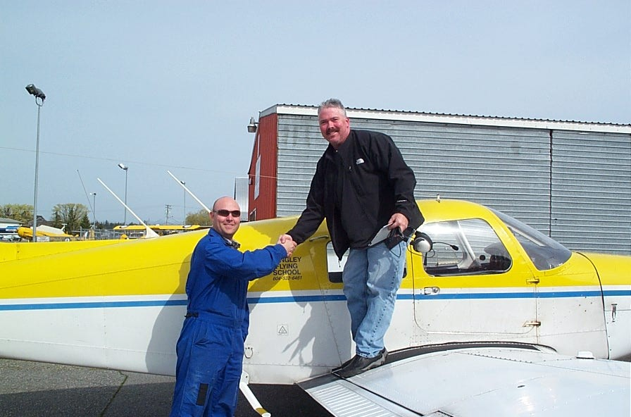 Drew Keeper receives congratulations from his Flight Instructor, Rod Giesbrecht, after completing his First Solo Flight in Cherokee GODP on March 27, 2010.