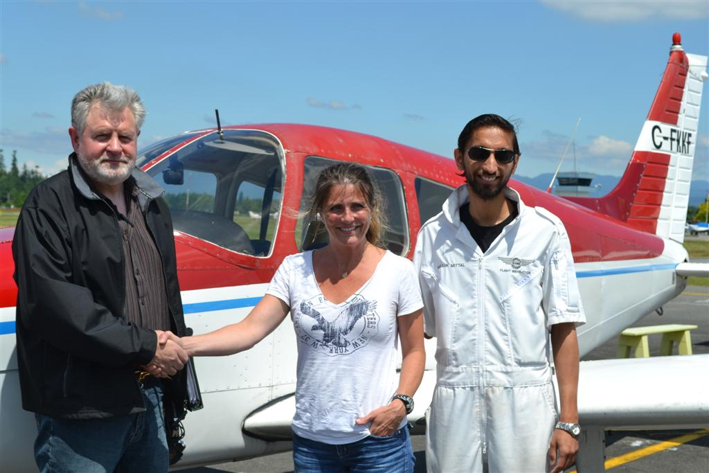 Katie de Sousa receives contgratulations from Pilot Examiner Paul Harris, and her Flight Instructor, Mayank Mittal, after the successful completion of Katie's Private Pilot Flight Test on June 26, 2011.  Langley Flying School.