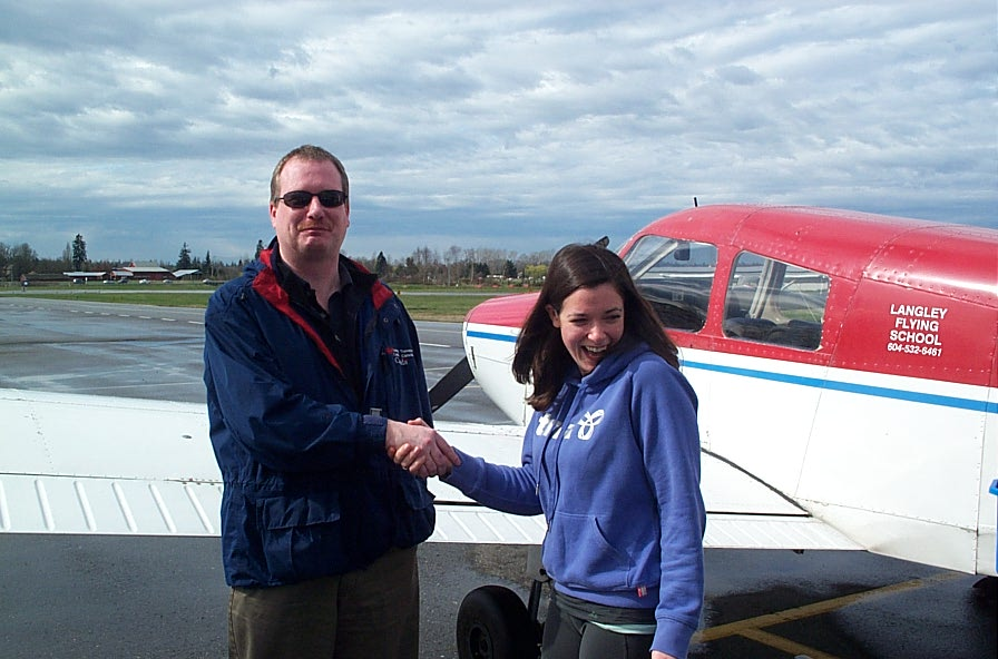 Naomi Jones receives congratulations from Transport Canada Inspector Peter Cox after the completion of Naomi's Class II Instructor Rating Flight Test. This achievement qualifies Naomi as a supervising Chief Flying Instructor. Langley Flying School.