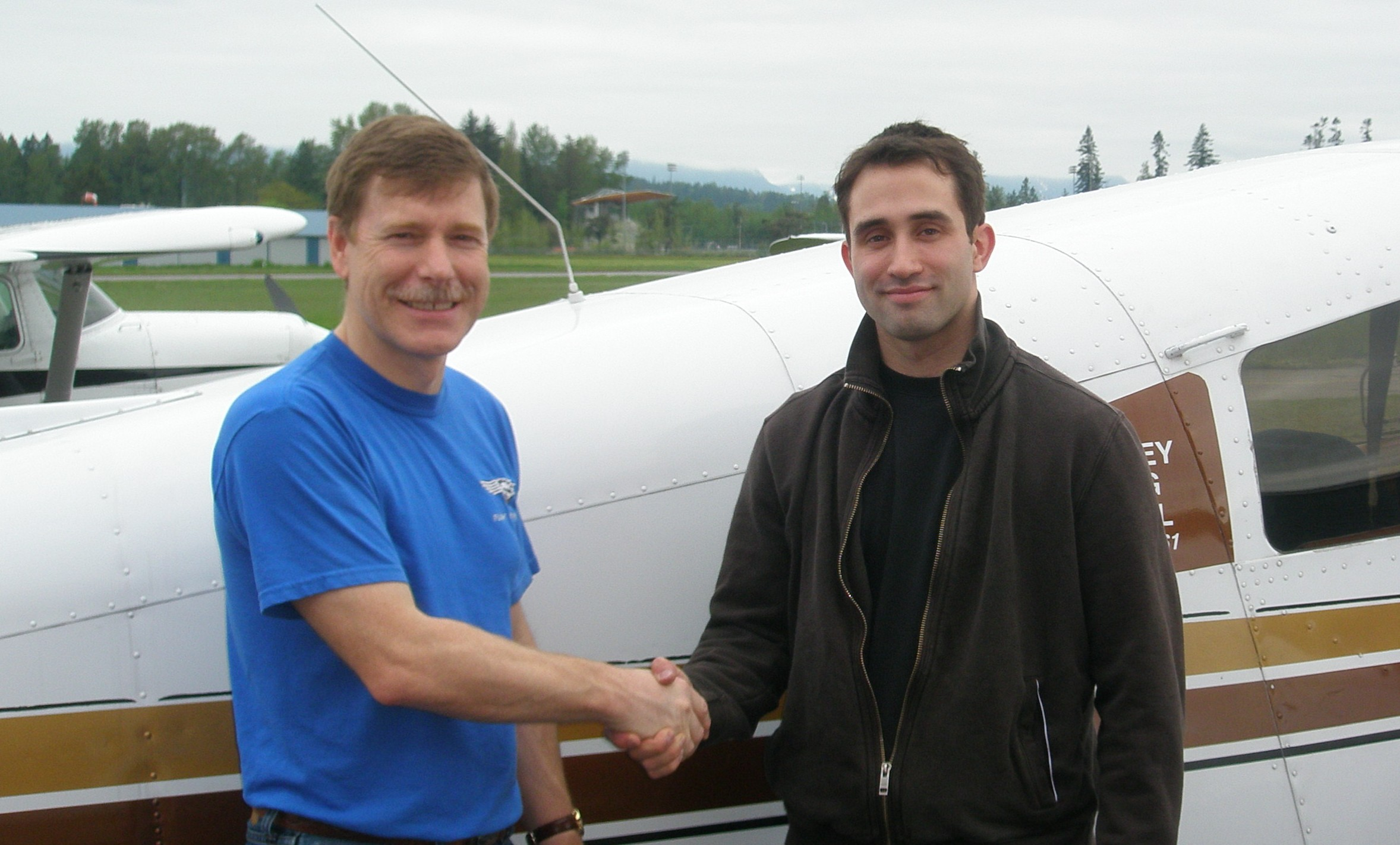 Shadrin Storness-Bliss receives contratulations from Flight Instructor Peter Waddington after the successful completion of Shad's Commercial Pilot Flight Test on May 15, 2008.  Langley Flying School.