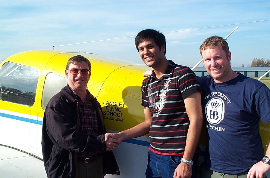 Suraj Canakapalli receives congratulations from Pilot Examiner John Laing and Flight Instructor Darren Ferguson.  Langley Flying School.
